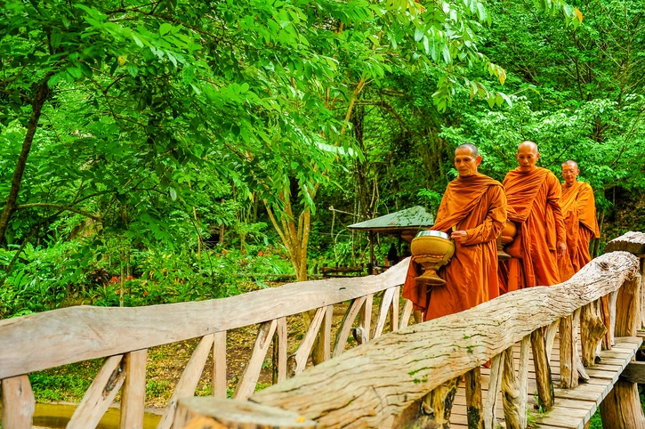 In the early morning hours, monks can be seen walking on their alms  round in Kanchanaburi, Thailand